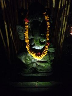 A gorgeous carved stone Ganesh with a garland of marigolds around his neck