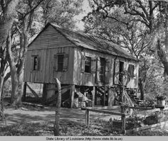 """Circa 1940s. Acadian or """"Cajun"""" cabin raised on piers in swamp. Location within Louisiana unknown.  NotesLife Photo by Peter Stackpole"""