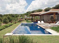 A piscina de pastilhas azuis e borda infinita invade parte da varanda, que dispõe de vista privilegiada. Próximo a sua margem, agapantos, quisquális, hamamélis e moreias preenchem o entorno. Projeto dos paisagistas Sérgio Menon e Caterina Poli.