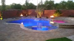 Sheer descents and a spillover spa wall are beautiful water features in this custom backyard pool/spa.