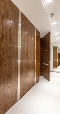 Alto full height flush fascia cubicles with doors and pilasters finished in dark oak veneer