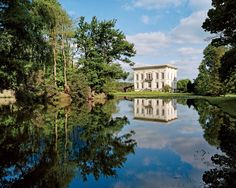The estate's original plantings have been enhanced to suggest a whimsically overgrown woodland that frames both the lake and the 1840s Neoclassical mansion.