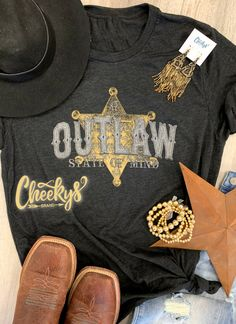 Adorable Outlaw tee on vintage black!! Think of all the adorable outfits that could be worn!! #cheekys #boutique #cheekysboutique #vintageblack #outlaw Trendy Boutique Names, Outlaw Women, Real Country Girls, Western Outfits Women, Cute Country Outfits, Aesthetic Shirts, Baby Boutique, Graphic Shirts, Branding