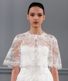 A strapless lace gown by Monique Lhuillier is accessorized with a stunning sheer lace cape.