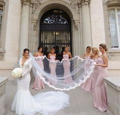 Pretty shot of the bride and her bridesmaids holding her veil