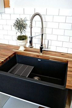 Black sink with butcher block countertop.