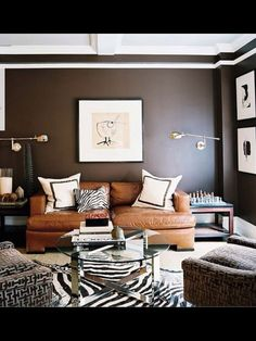 Dark walls, Camel Leather Sofa, Brass Wall Lamps, and large Scale Art create a Handsome Room.