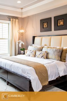 A gold padded headboard provides a backdrop for subtle, patterned throw pillows…
