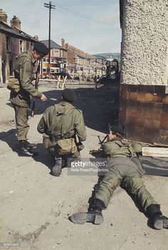 View of British Army soldiers patrolling in front of a barricade of burnt out buses and barbed wire on a residential street in Belfast, Northern Ireland following a night of sectarian rioting and disturbances in the city on 19th August 1969.