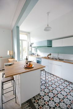 Mosaic and cement tiles add interest, depth to this white and powder blue kitchen.