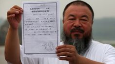 In a park in Beijing, Chinese artist Ai Weiwei holds a copy of a government document informing him of the expiry of his bail term. June 21, 2012.