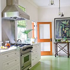 Kitchen with green painted floors, stainless steel appliances and orange wood back door.