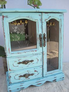 """Cute chalk painted Turquoise distressed and sealed with wax vintage wood jewelry box. Stainless glass window style front door. Door opens and there is an area for hanging necklaces with a mirror. Half door on opposite side with area for rings and a mirror backing. Two drawers below. Very nice and clean condition with gray velveteen lining. Measures 11 3/8"""" tall x 9 1/4"""" wide by 5 deep. By: OhSoShabbyDecor $45.00"""