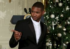 Hitmaker Usher cuts a dashing figure as he points at someone while attending the 2015 Kennedy Center Honors Reception at the White House