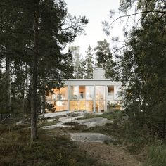 This concrete house that stands in a pine grove on Swedish coastline features a glazed facade to give glimpses of the Baltic sea through the tree trunks.