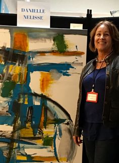 """Featured #artist Danielle Nelisse at North Park Dec 2015 #rayatnight holiday celebration in San Diego, California standing with """"CO2 350+"""" #abstract #painting in acrylic and oil"""