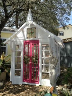 Greenhouse constructed from salvage windows, stained glass, old painted pink doors and ceiling tin. A beauty!