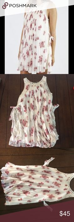 Free people Floral umbrella dress Woman's size small Floral pleated umbrella dress. Like new. Only wear issue is on the the tag itself. Lace trimmed neckline and lace section on each side with ties. Lined. The chest measures 20 inches and this is 32 inches long. Cream and maroon. Free People Dresses Mini