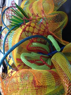 Multi color Deco mesh wreath with yellow/blue/green/red/orange. Green and red mesh tubing, yellow flower and blue roping.