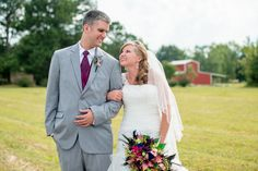 Peacock inspired wedding with portraits in front of a red barn.