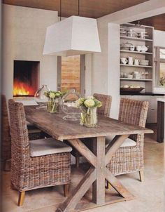 Verdigris Vie. Rustic wood dining table and wicker chairs. Contemporary chandelier and fireplace