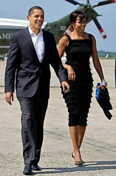 "Barack Obama escorts his first lady to Air Force One for a date night in New York City that included a private dinner before watching the play ""Joe Turner's Come and Gone."" MIchelle Obama livened up her frilly black dress with a small blue clutch."