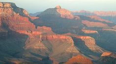 Grand Canyon National Park.  Looking east from Mather Point during sunset; canyon formations bathed in orange light.