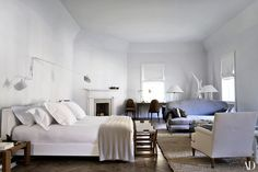 In the master bedroom, a custom Hermès bench sits at the foot of the Christian Astuguevieille bed. Serge Mouille two-arm sconce; Louis XV sofa in silk velvet; Jansen bergère upholstered in unprimed artist canvas.