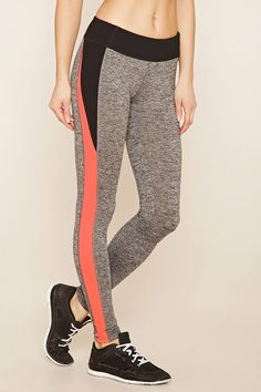 A pair of stretch knit athletic leggings featuring a hidden key pocket, moisture management, and colorblock panels at its sides and waist.