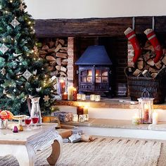 A country inglenook complete with woodburning stove and twinkling candlelight from votives and lanterns is the perfect Christmas setting.