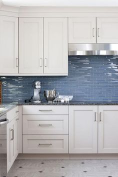 White and blue kitchen features white cabinets adorned with satin nickel  pulls paired with black .