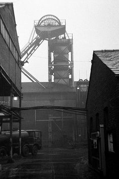 Friday 12th December 1969.The headgear of a colliery at Thatto Heath, near St Helens, Lancashire. As you will know, the airtight casing within the headframe tells us that this is the top of the upcast shaft. A huge fan sited near the top of this shaft (but with a seperate outlet) draws fresh air down the mine's second (downcast) shaft. Underground, airtight doors route the fresh air through the workings.  Usually the upcast shaft is used for winding men and materials;.Ravenhead Colliery.