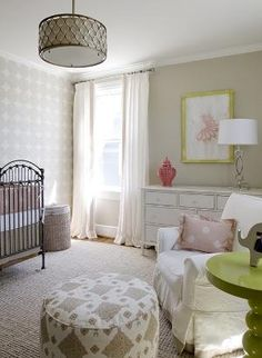 Sweet pink & tan baby girl's nursery with tan walls paint color, antique crib, pink & gray crib bedding, ivory & silver gray circles wallpaper, white curtains window panels with coral pink Greek key trim, jute rug, white glider with pink ruffled pillow, glossy green lacquer spindle table, white chest, coral pierced carthage lantern, gray & pink pouf, yellow & pink art and beehive drum pendant. by Angelic Harmony
