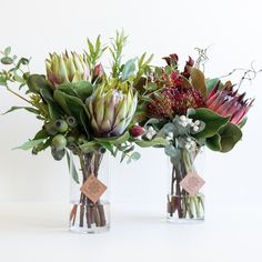 Artificial Australian native arrangements with burgundy and green protea, gum nut, tetragona, dollar gum and leucadendron set in crystal clear water resin.