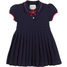 Baby girls navy blue dress by Gucci. It is made in a soft textured cotton piqué with buttons to fasten on the front and a full pleated skirt. The collar has red and blue stripes with a lacy woven trim and a grosgrain ribbon bow. The soft ribbed cuffs have a red stripe.