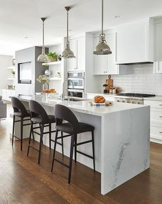 Three dark gray velvet stools sit at a white kitchen island fitted with a calcutta quartz waterfall countertop finished with a stainless steel sink with a polished nickel gooseneck faucet illuminated by three Restoration Hardware Harmon Pendants. Quartz Countertops, Kitchen Countertops, Home Decor Kitchen, New Kitchen, Kitchen Sink, Timber Kitchen, Kitchen Worktop, Wooden Kitchen, Kitchen Ideas