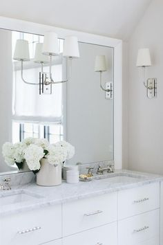 A white dresser-like bath vanity fitted with polished nickel pulls is topped with a marble countertop holding sinks beneath polished nickel cross handle faucets.