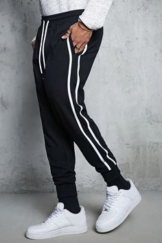 A pair of French terry joggers featuring side stripes, on-seam pockets, an elasticized drawstring waist, and ribbed knit ankle cuffs. Track Pants Mens, Track Suit Men, Dope Outfits, Sport Outfits, Jogger Pants Style, Latest Mens Wear, Men Trousers, Fashion Joggers, Best Mens Fashion
