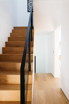Simple wood stairs with a black handrail connects the various levels of this modern house. #Stairs #WoodStairs #BlackHandrail