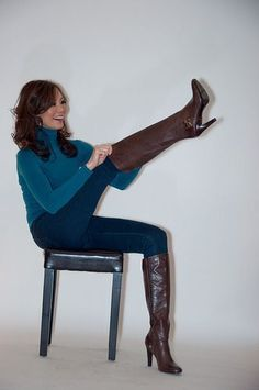 Girl in turtleneck sweater and jeans pulling on brown leather high heel boots #highheelbootsandjeans
