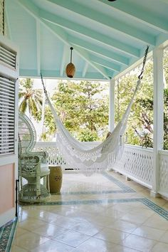 A small white painted porch with a white macrame hammock, peacock chair and white fence.