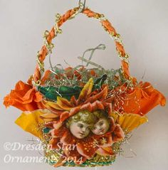 Chrysanthemum with Children's Faces on Orange Ruffled Crepe Paper Basket   http://victorianornaments.com