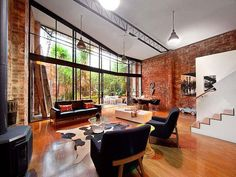 Living room of converted warehouse in Melbourne with brick walls and large glass wall Beautiful Brick Walls: Warehouse Conversion in Fitzroy Conceals Twin Delights