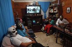 Mexican lucha libre wrestler Estrella Dorada (Spanish for Golden Star) sits with her four sons at her house on the outskirts of Mexico City, September 28, 2011. Estrella Dorada is married to a wrestler and three of her sons are also wrestlers. She has been wrestling for 18 years. They are wearing their masks at home to preserve their anonymity.  REUTERS/Carlos Jasso