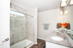 """Framed shower door package with square straight set field tile, 4"""" horizontal accent linear glass, framed shower door with fiberglass insert. Standard vinyl floors, granite countertops and double sinks."""