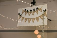 hiding the basketball backboard in wedding reception--removed hoop, covered with white sheet, and decorated with a banner! sad that the flower garland fell...oh well! :)