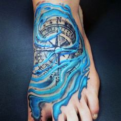 Detailed compass and pale blue water waves foot tattoo