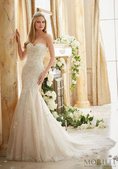 Delicate floral lace sweeps the skirt and train of this gorgeous Morilee Fit and Flare.  Sweetheart neck and with beaded bodice.  Would look stunning in a garden setting.  Designed by Madeline Gardner.  Style 2886.