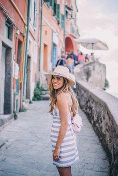 Gal Meets Glam Cinque Terre - Manarola and Riomaggiore. Dress by Lovers + Friends and hat by Hat Attack