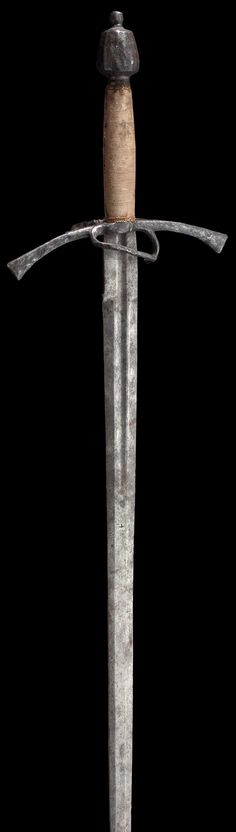 A hand-and-a-half sword. 16th century. Double-edged blade, flat fullers at the forte, with brass-inlaid orb mark on the obverse side. Long quillons with bars on each side. Added cloth covered grip, unassociated fluted pommel with large rivetted finial. Pommel and quillons with signs of corrosion. Weapon composed of old parts. Length 107 cm.